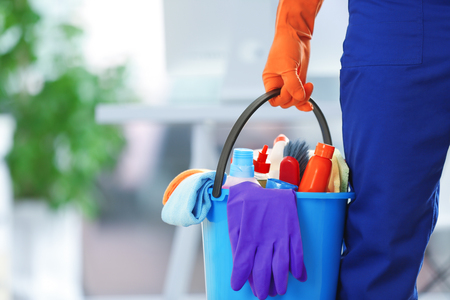Foto de holding cleaning products and tools on bucket, close up - Imagen libre de derechos