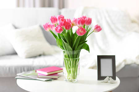 Foto de Fresh bouquet of tulips on a coffee table - Imagen libre de derechos