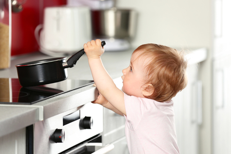 Photo pour Little child playing with pan and electric stove in the kitchen - image libre de droit