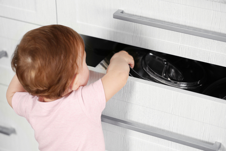 Photo for Little child playing with drawer - Royalty Free Image