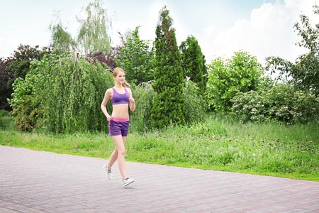 Photo pour Sporty woman jogging at park on a sunny day - image libre de droit