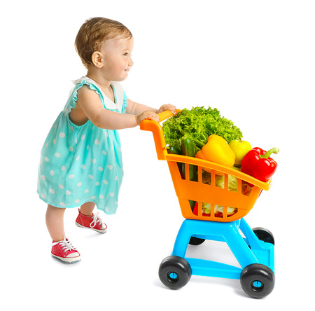 Photo pour Cute baby girl with vegetables in supermarket trolley, isolated on white - image libre de droit