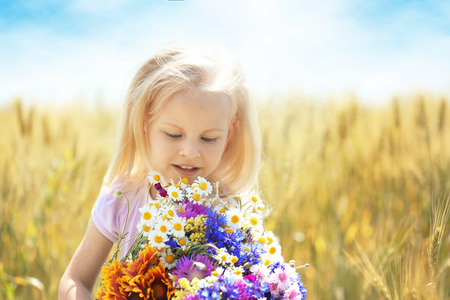 Photo for Little girl with bouquet of flowers in the field - Royalty Free Image