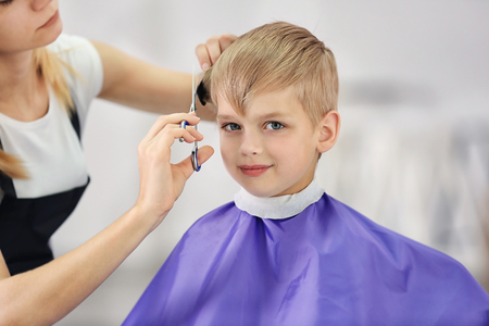 Photo pour Hairdresser's hands making hairstyle to child - image libre de droit