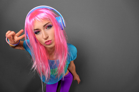 Photo for Glamour young woman with headphones on grey background - Royalty Free Image