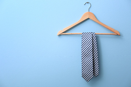 Photo for Male tie hanging on the rack, blue background - Royalty Free Image