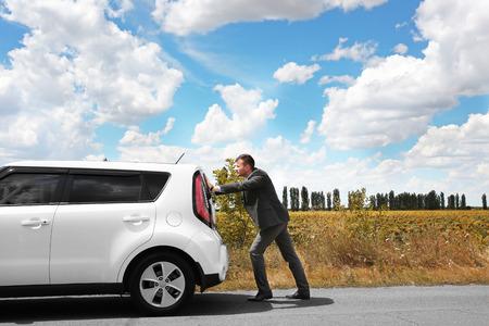Foto de Man pushing damaged car - Imagen libre de derechos