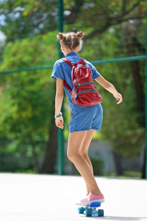 Photo pour Cute young girl riding skateboard in sports ground - image libre de droit