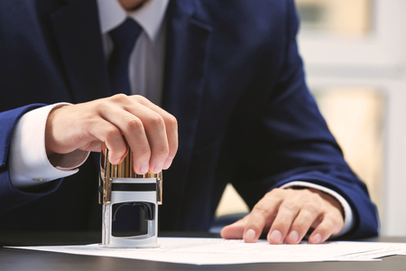 Photo pour Notary public in office stamping document - image libre de droit