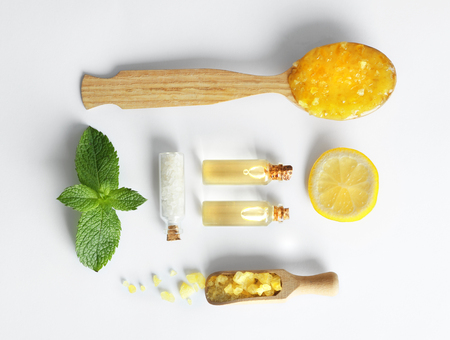 Photo for Wooden spoon with scrub, lemon slice, mint, sea salt and bottles of oil isolated on white - Royalty Free Image
