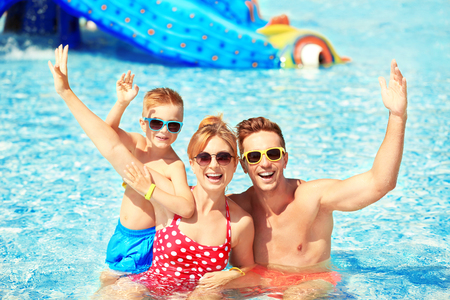 Photo pour Happy family in swimming pool at water park - image libre de droit
