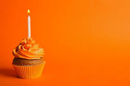 Photo pour Fresh tasty cupcake with candle on orange background - image libre de droit