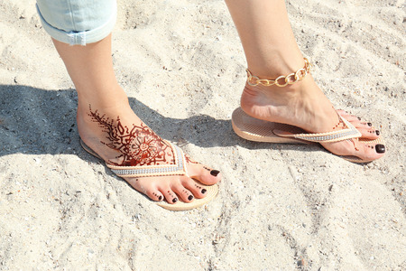 Photo pour Female legs with henna tattoo on beach sand background - image libre de droit