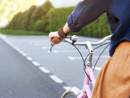Young woman riding bicycle along road, close up view