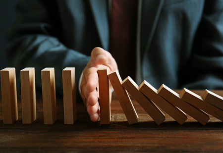 Photo for Businessman hand trying to stop toppling dominoes on table - Royalty Free Image