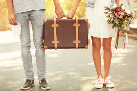 Photo pour Just married couple holding vintage suitcase and walking in park - image libre de droit