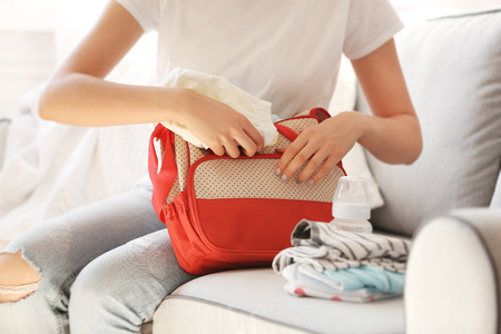 Photo pour Woman packing her bag with child stuff on couch - image libre de droit