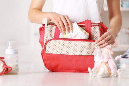 Foto de Woman packing her bag with child stuff - Imagen libre de derechos
