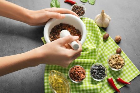Foto de Female hands grinding spices in mortar - Imagen libre de derechos