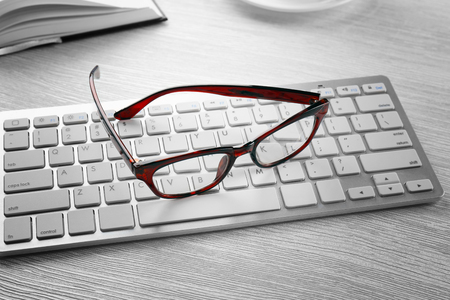 Photo pour Glasses and keyboard on wooden table. Healthy eyes concept - image libre de droit