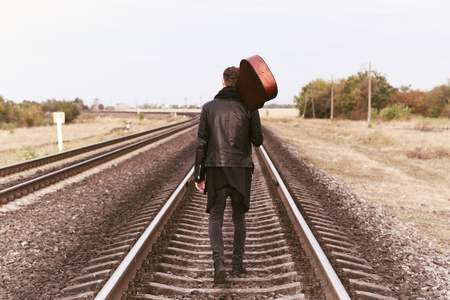 Photo for Handsome man with guitar on railroad - Royalty Free Image