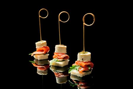 Photo pour Gourmet canapes on black background - image libre de droit
