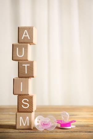 Foto de Wooden cubes with word autism and pacifiers on light background - Imagen libre de derechos