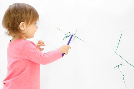 Foto de Cute little girl drawing on light wall - Imagen libre de derechos