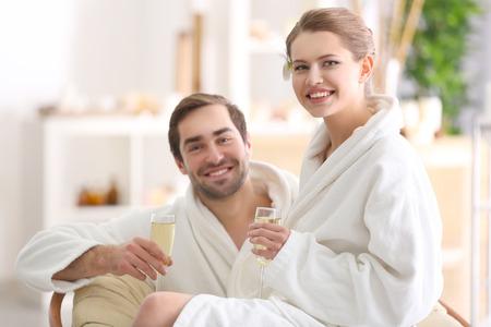 Foto de Young happy couple drinking champagne in spa salon - Imagen libre de derechos