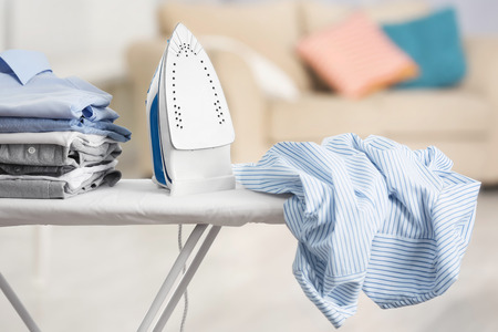 Photo pour Electric iron and pile of clothes on ironing board - image libre de droit