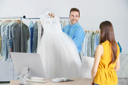 Photo pour Man working with customer in dry-cleaning salon - image libre de droit