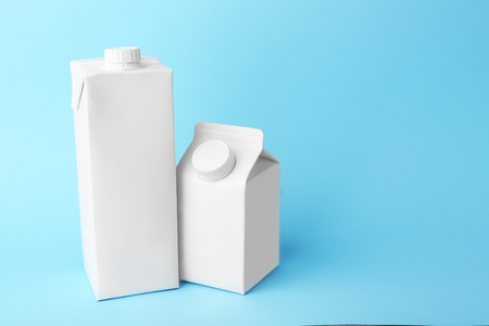 Photo pour Two simple milk boxes on color background - image libre de droit