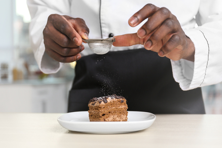 Photo for African American chef sifting sugar on tasty cake in kitchen, closeup - Royalty Free Image