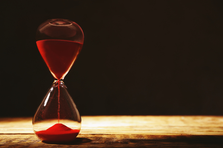 Photo for Time passing concept. Crystal hourglass with red sand on wooden table and dark background - Royalty Free Image
