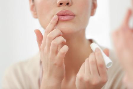 Photo pour Woman applying hygienic lip balm near mirror - image libre de droit