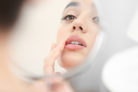 Photo for Young woman with cold sore looking in mirror at home - Royalty Free Image