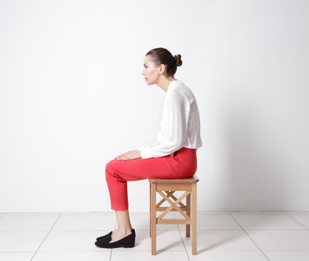Photo pour Incorrect posture concept. Young woman sitting on stool against white wall background - image libre de droit