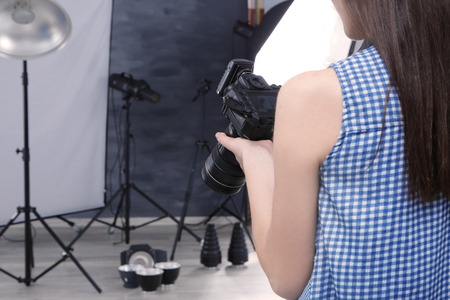 Photo for Young professional photographer with camera in studio - Royalty Free Image