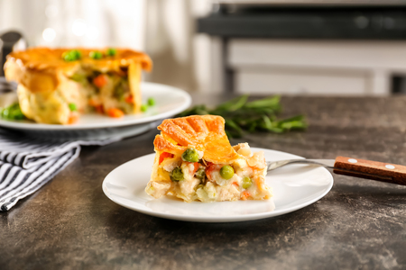 Photo for Plate with piece of delicious chicken pot pie on kitchen table - Royalty Free Image