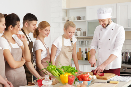 Photo pour Male chef and group of people at cooking classes - image libre de droit