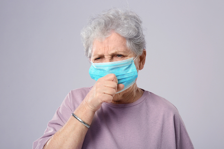 Photo for Portrait of coughing elderly woman wearing protective mask on grey background - Royalty Free Image