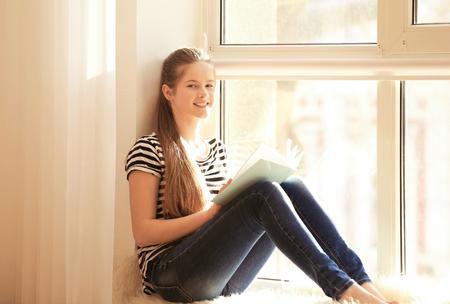 Foto de Pretty teenager girl sitting on windowsill at home - Imagen libre de derechos