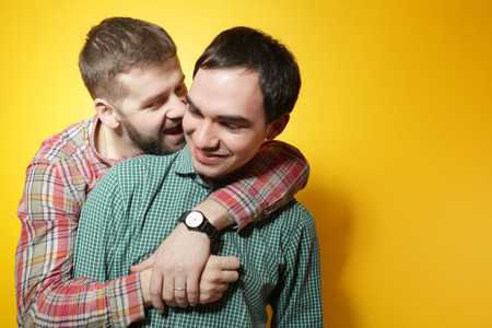 Foto de Happy gay couple posing on yellow background - Imagen libre de derechos