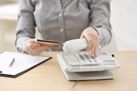 Foto de Woman with bank card calling the clients support center while sitting in office - Imagen libre de derechos