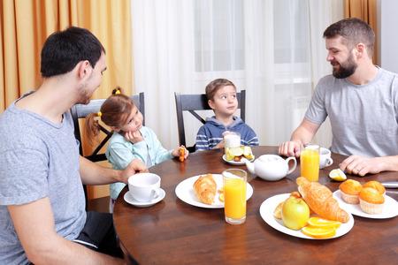 Photo pour Male gay couple with children having breakfast in kitchen - image libre de droit