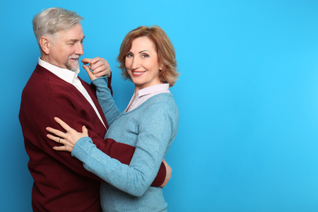 Foto de Happy senior couple dancing on color background - Imagen libre de derechos