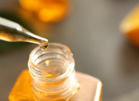 Foto de Perfume bottle and pipette with essential oil on blurred background - Imagen libre de derechos