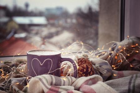 Foto de Cup of hot tasty coffee with garland and warm plaid on windowsill - Imagen libre de derechos