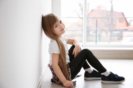 Foto de Cute little girl sitting on floor near window. Fashion concept - Imagen libre de derechos