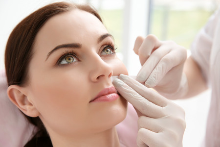 Photo pour Woman having hair removal procedure on face with wax depilatory in salon. Depilation concept - image libre de droit